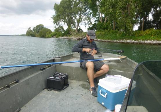 A person sitting in the front of a boat putting something in a plastic bag. There is a long pole with spikes on one end balanced in their lap.