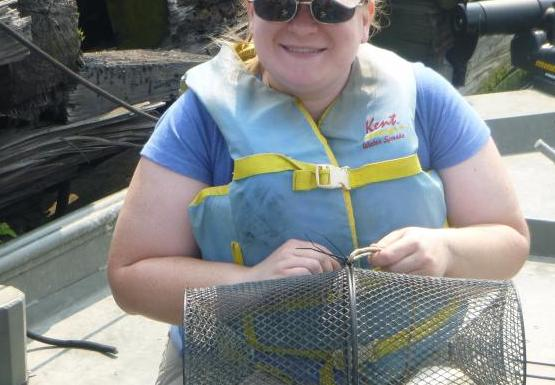 A person sitting on a small boat near a wall. They have a cylindrical mesh cage on their lap.