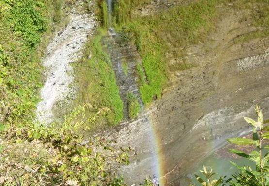 A tall but very narrow waterfall with a rainbow.