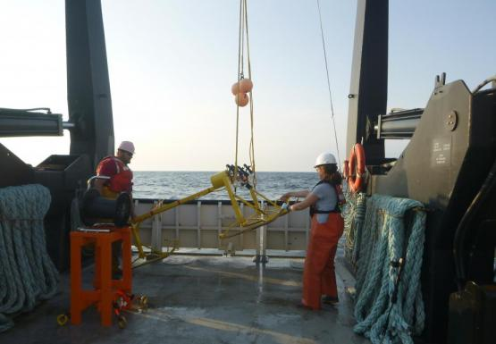 Two people help steady a metal frame as it is lifted off the deck of a large boat by a winch.