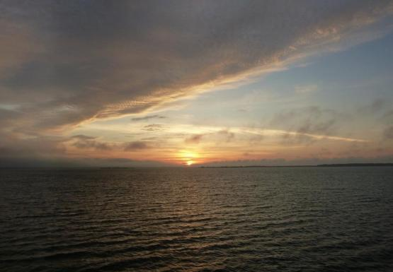 Sunrise over water. The sun is a light yellow and the clouds cover half of the sky.