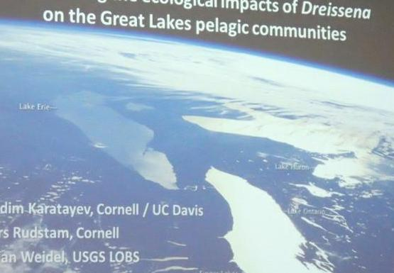 "picture of a presentation projected on a screen. There is an aerial photo of large lakes with text that says ""Monitoring the ecological impact of Dreissena on the Great Lakes pelagic communities"""