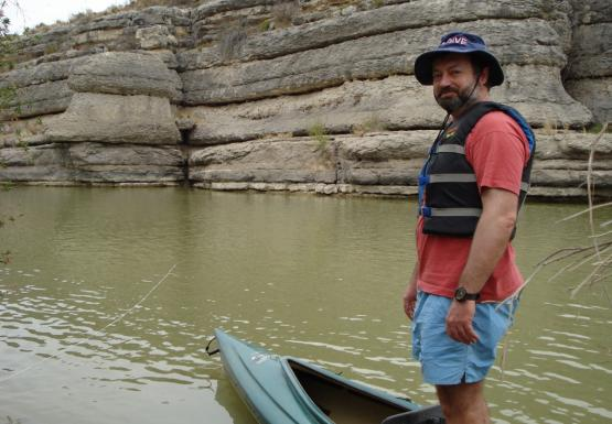 a man stands on a canoe in water. There is a cliff behind him.