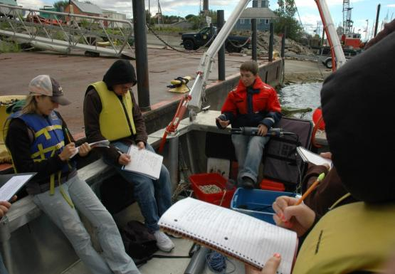 Students sit on a boat tied up at dock while a person in an orange float coat holds up a grey research instrument