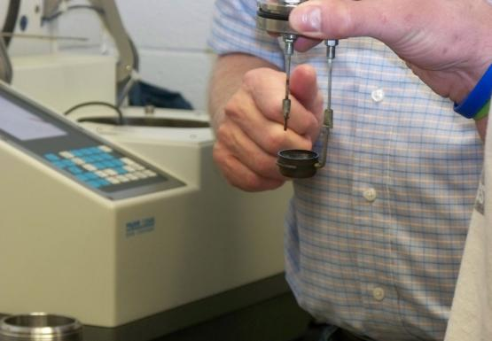 Closeup of someone's hands holding a metal lid with two rods hanging from it. At the bottom of one rod is a small metal cup. In the background is a lab instrument