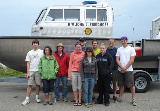 "Ten people stand in front of a boat on a trailer. The boat is named ""R/V John J. Freidhoff"""