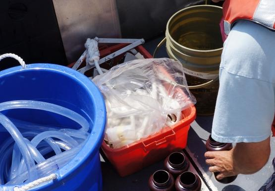 A person in a life jacket lines up bottles on the deck of a boat. There is a tub with a tube in it, and two other buckets nearby.