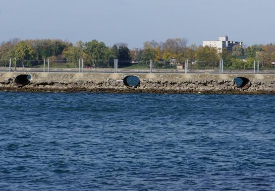 A breakwall that separates the canal (fore) from the the river (back). At least a foot of gravel is visible below the culverts in the breakwall. There is an area of wet gravel above the current water level, as if the water level has fallen.