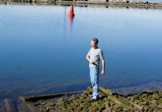 A person stands on algae-covered stone and wood cribbing by the water. They gesture at waist level.