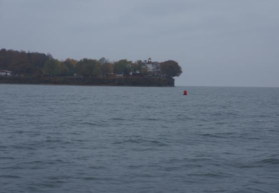 A cliff with trees and a lighthouse, surrounded with water. There is a red navigational buoy in the water.