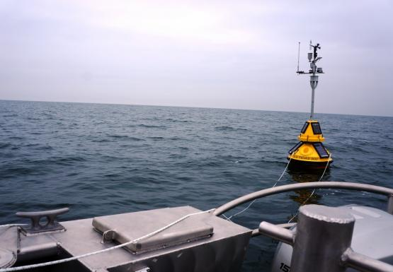 A yellow buoy seen from the back of the boat. There are ropes going from the buoy to the boat.