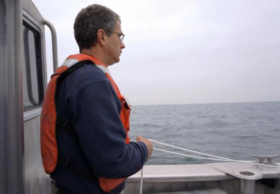 A person in a life jacket stands on the back of a boat holding a rope