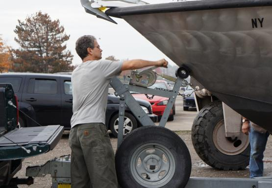 A person stands by a boat on a trailer. They are turning a crank to tighten a strap between the trailer and the boat.