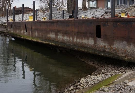 A barge that is used as a dock. The high water level is visible at least a foot above the water, and the water is below the bottom of the barge by about a foot.