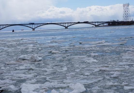 Ice chokes the river near the breakwall. There is a bridge in the distance.