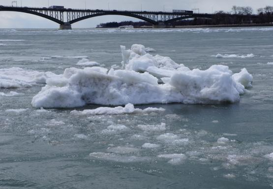 A large chunk of ice in an icy river. There is a bridge in the distance.