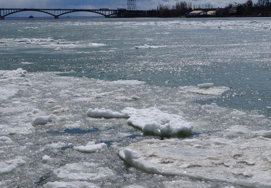 Large chunks of ice in the river. There is a bridge in the distance.