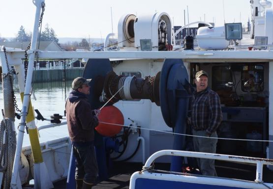 Two people on the back of a boat wind rope onto a large reel.