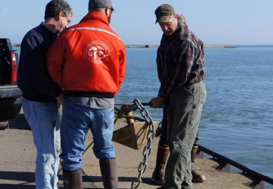 Three people lift an anchor on a metal rod. They are near water.