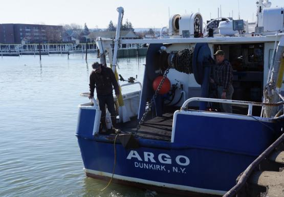 "Two people coil chain onto a large reel on the back of a boat. The anchor is just below the deck. The boat is named ""Argo"""