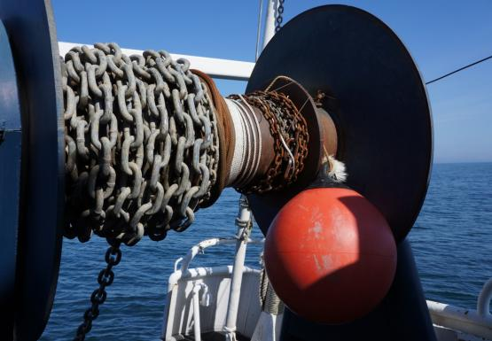 Chain, rope, and an orange float coiled on a large reel