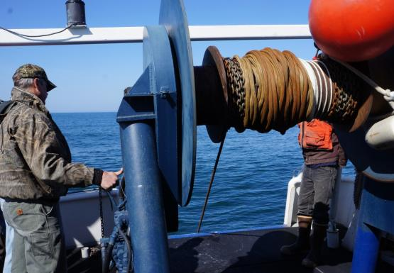 A person operates a large reel on a boat to lower a rope into the water