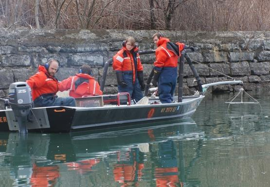 Four people in orange float suits on a shallow boat. The boat has a railing at the front and two booms with wires hanging into the water. Two people stand at the front of the boat, one sits with a net, and the last is at the back of the boat by the controls