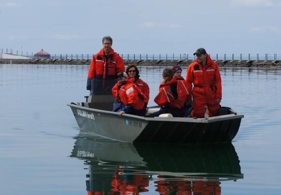 A group of people in orange float suits aboard a shallow green boat on glass-calm water