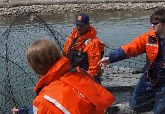 A group of four people in orange float suits pulling a net with hoops onto a boat