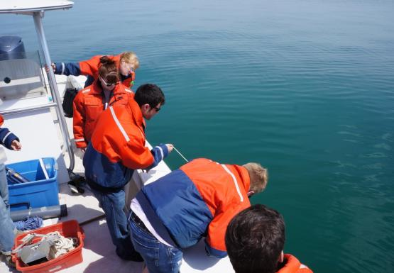 People in orange float coats lean over the side of a boat to watch one of them deploy some equipment