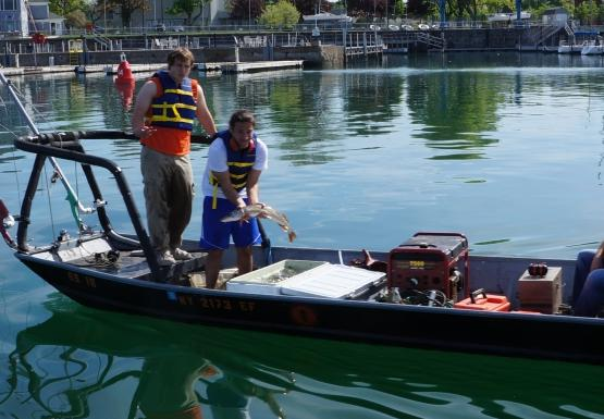 Three people on a shallow boat with a railing. One person operates the motor while two stand in the front. One person is standing over a white cooler and holding up a large fish.