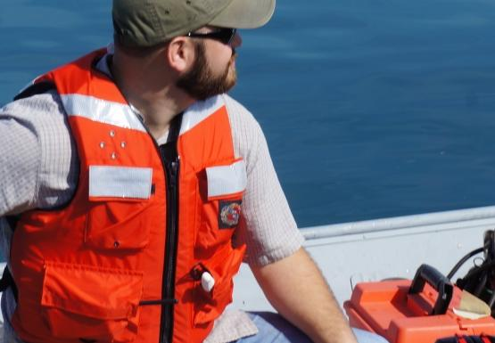 A person sitting the the back of a boat, operating the motor.