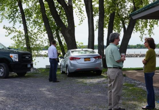 A few people stand talking in a parking lot by the water