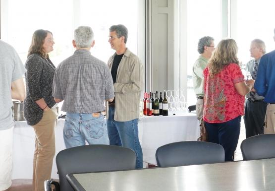People stand talking to each other in a room with a wall of large windows. There is a table with refreshments behind them