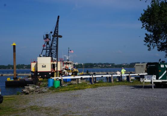 A tug and a barge with a crane approach a dock