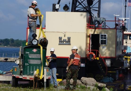 Crew members put straps on a generator while a crane stands by behind them.