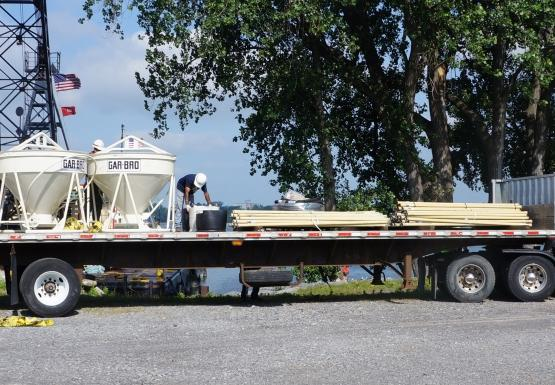 A truck arrives with three concrete vats and some planks. There is a crane behind them.