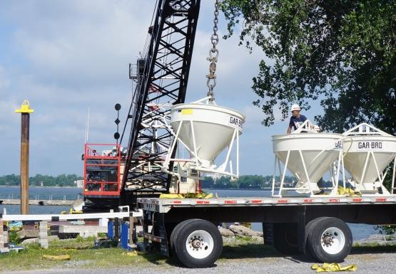 A crane lifts a concrete vat off the flatbed of a truck. There are two other concrete vats.