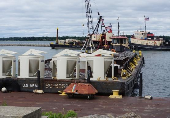 The front of a barge with some concrete equipment waits at a dock. There is a tug with a barge with a crane in the distance behind it.