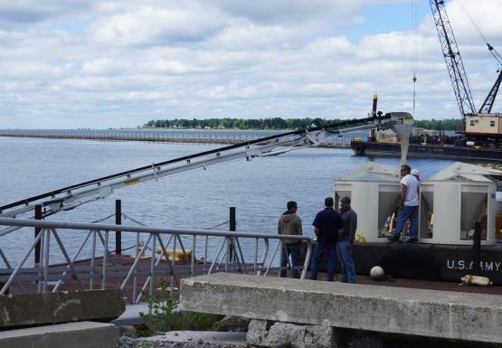 A cement truck uses a long arm to load concrete vats on the front of a barge at the waterfront