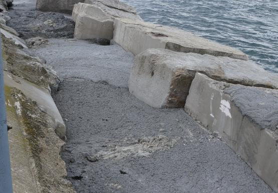 Blocks and concrete added to stabilize outer side of Bird Island Pier
