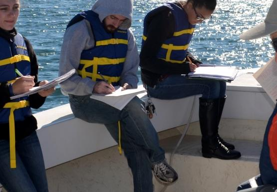 A group of students on a boat take notes while a person holds up a long grey instrument and gives a lecture