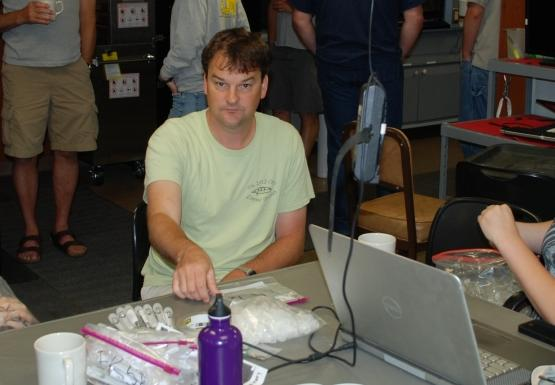 Several people sit or stand inside a lab.