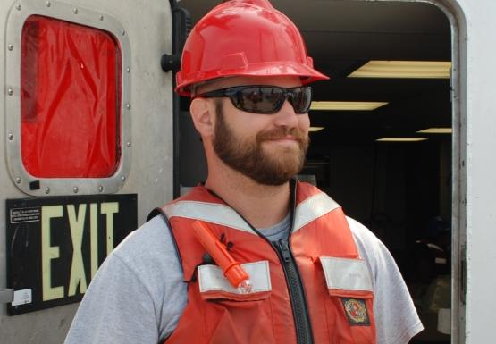 "A person wearing a hard hat and life jacket stands by a bulkhead door labeled ""exit"""