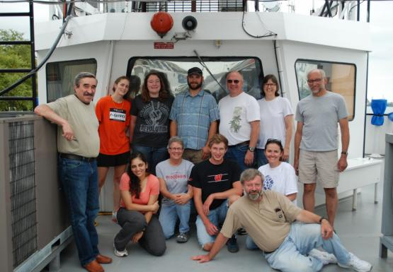 Twelve people pose for a group picture near the bridge of a boat