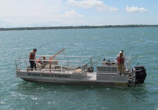 "Three people on a small boat with railings labeled ""US Army Corps of Engineers."""