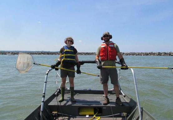 Two people holding nets at the front of a boat. They are wearing safety gear.