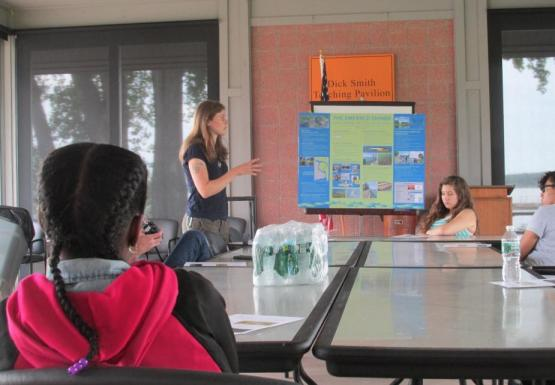 A person standing up talking by a poster in front of several younger people sitting around a table.