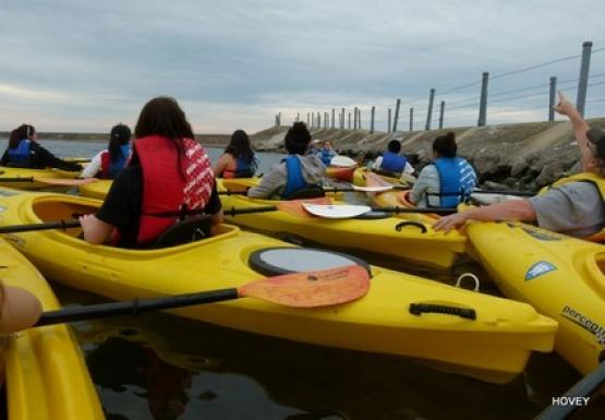Several people in kayaks clustered near a break wall.