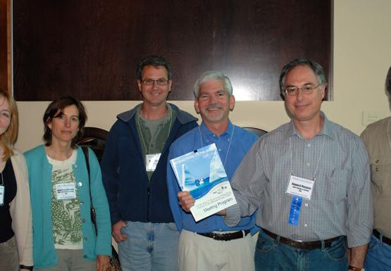 six people pose for a picture indoors, while one holds up a program booklet